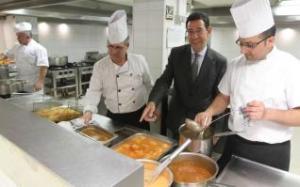 El director del Regente, entre varios cocineros del establecimiento, mostrando algunos de los platos calientes que preparan cada día.  LARS TER MEULEN