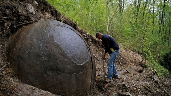 Suad Keserovic cleans a stone ball in Podubravlje village near Zavidovici, Bosnia and Herzegovina April 11, 2016. Keserovic claimed that the stone sphere is 3.30 meter in diameter and the estimated weight of it is about 35 tons. (REUTERS/Dado Ruvic)